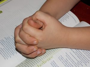 child-hands-over-bible